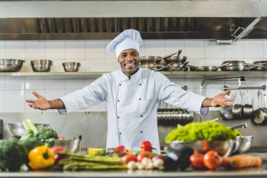 handsome african american chef standing with open arms at restaurant kitchen