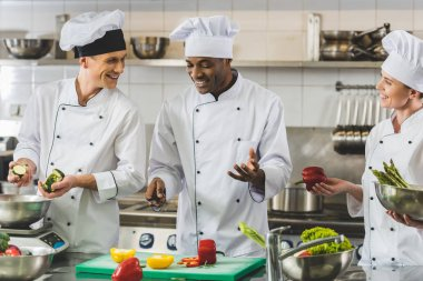 smiling multicultural chefs talking at restaurant kitchen
