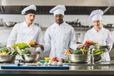 multicultural chefs at restaurant kitchen with vegetables on foreground