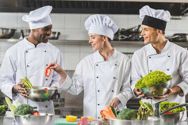 happy multicultural chefs cooking vegetables at restaurant kitchen
