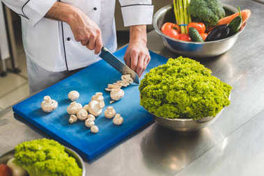 cropped image of chef cutting mushrooms at restaurant kitchen