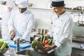 happy multicultural chefs working at restaurant kitchen
