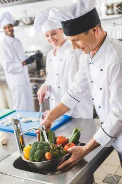 smiling chef washing vegetables at restaurant kitchen