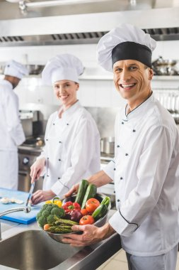 smiling chefs looking at camera at restaurant kitchen