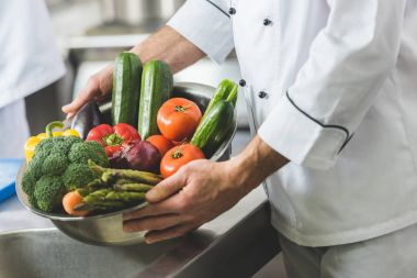 cropped image of chef holding bowl with vegetables at restaurant kitchen