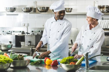 smiling multicultural chefs cutting vegetables at restaurant kitchen and looking at each other