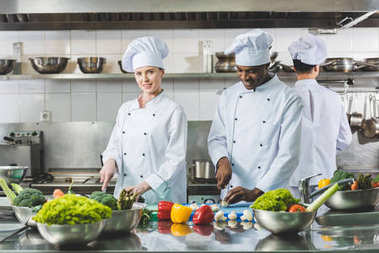 multicultural chefs cutting vegetables at restaurant kitchen