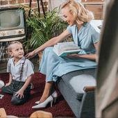 Fényképek boldog szőke nő könyvet olvas, és nézett aranyos kis fia játszik a szőnyeg otthon, 1950-es évek stílusú családi