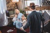 szelektív összpontosít, anya, két gyerek együtt játszanak, és látszó-on apa jön haza, 1950-es évek stílusú