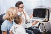 1950er Jahre Familie mit einem Kind mit Laptop mit leeren Bildschirm zu Hause