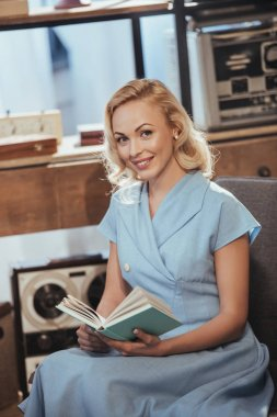 beautiful blonde woman in blue dress holding book and smiling at camera, 50s style
