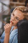 Fotografie schöne blonde Frau in Brillen halten Zigarette und wegsehen, 50er Jahre Stil