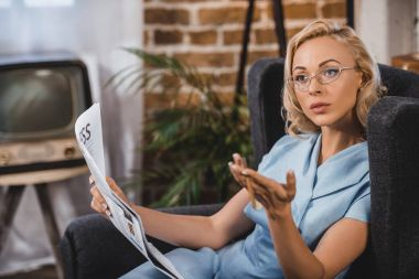 beautiful blonde woman in eyeglasses holding newspaper and looking away, 1950s style
