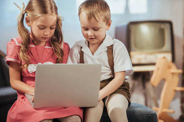 cute little children in 1950s style clothes using laptop together at home