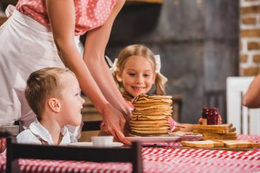 Cropped shot of mother holding plate with delicious pancakes and cute little kids sitting at table stock vector