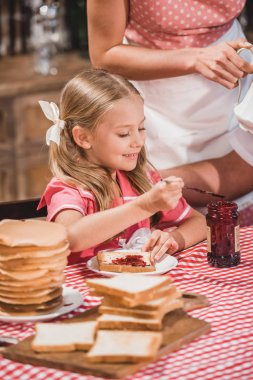 cute smiling little girl eating delicious toast with jam for breakfast