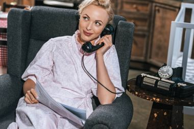 smiling blonde woman in robe holding newspaper and talking by vintage telephone at home