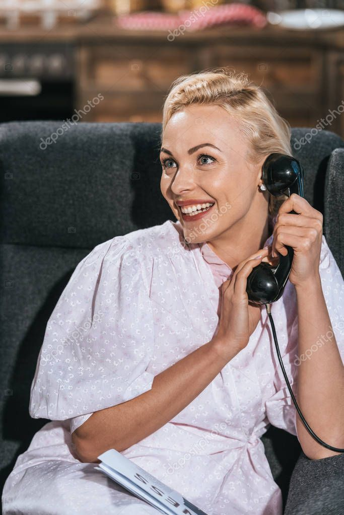 Happy blonde woman in robe talking by vintage telephone and looking away