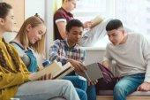A multikulturális középiskolás középiskolás diákok csinál házi feladatot, iskolai szünetben csoport