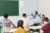 Fotografie Rear view of multiethnic high school teenage students and african american teacher with wide arms