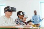 multikulturelle Schulkinder mit Virtual-Reality-Headsets und afrikanisch-amerikanischer Lehrerin, die dahinter steht