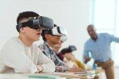 Seitenansicht des multikulturellen Schulkinder mit virtual-Reality-Kopfhörer und sprechen die Lehrer hinter