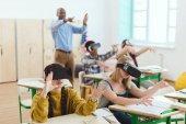 Tizenéves középiskolás segítségével virtuális valóság fejhallgatók, és intett a tanár osztálytermi mögött