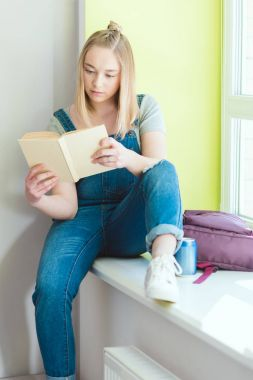 Teenage schoolgirl reading book and sitting on window sill with soda and backpack