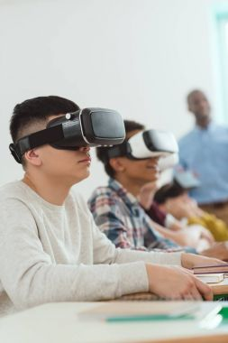 Side view of multiethnic high school pupils using virtual reality headsets and teacher standing behind