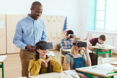 Standing teacher and multicultural high school teenage students using virtual reality headsets