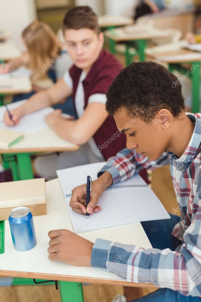 Elevated view of african american teenage schoolboy writing in textbook and classmates on behind stock vector