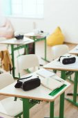 Photo Elevated view of virtual reality headsets on tables in empty classroom