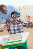 Fotografie Afrikanische amerikanische Lehrer halten Schultern der Schuljunge mit virtual-Reality-Kopfhörer