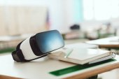 Photo Closeup shot of virtual reality headset on table with textbook and pencil in classroom