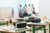 Fotografie Virtual-Reality-Headsets an Tischen mit Lehrer und Schülerinnen und Schüler im Klassenzimmer hinter