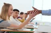 Fotografie Oříznutý obraz afrických amerických učitele, přičemž vysoká pět na usmívající se dospívající školačka