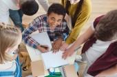 Fotografie vysoký úhel pohled studentů středních škol pomoci jejich spolužák s domácími úkoly