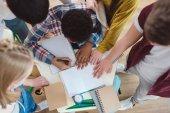 felülnézet középiskolás diákok segíti a osztálytársa, a házi feladat