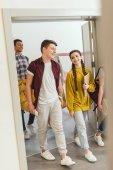 Fotografie multiethnic group of high school students walking by school corridor on break