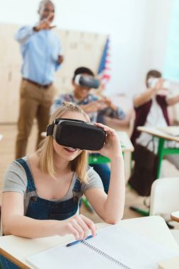 Teenage schoolgirl using virtual reality headset with male classmates and teacher behind