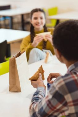 high school students eating sandwiches at school cafeteria