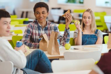 multiethnic group of high school students chatting while taking lunch at school cafeteria