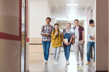 group of high school classmates walking by school corridor