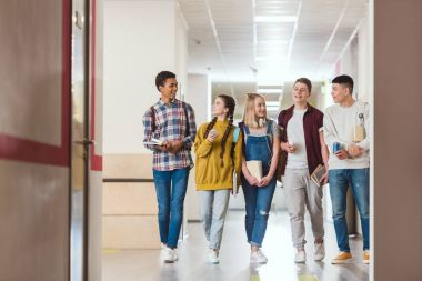 group of smiling high school classmates walking by school corridor together