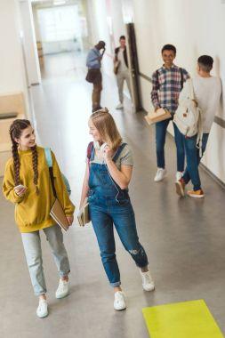 group of multiethnic high school students spending time at school corridor during break