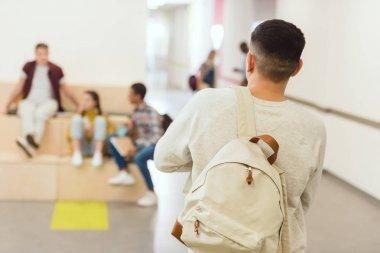 rear view of high school student standing at school corridor