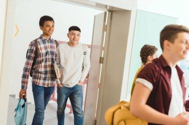 multiethnic high school students walking by school corridor