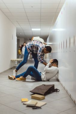 schoolboy being bullied by classmate in school corridor under lockers while other boy running to help him