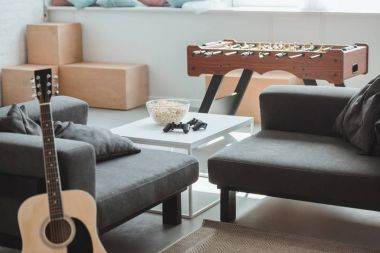 interior of modern living room with guitar, armchairs, table football and table with joysticks and popcorn