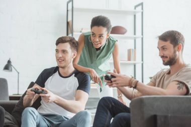 young african american woman watching two men playing video game with joysticks in hands